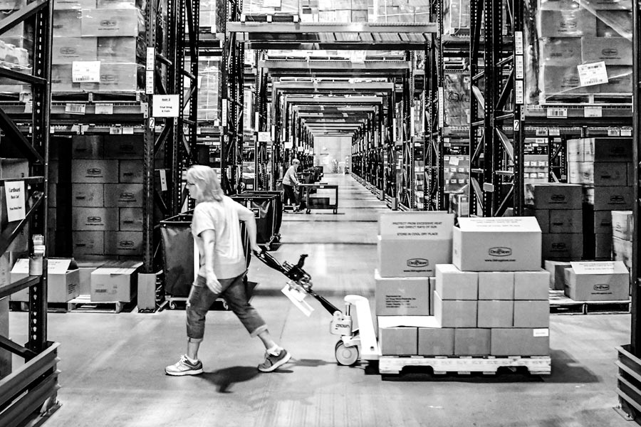 A large warehouse with workers hauling pallets